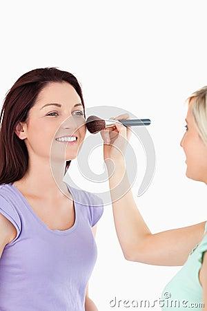 Gorgeous Women applying make-up