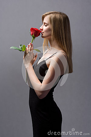 Gorgeous young blond woman holding rose.