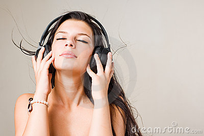 Gorgoeus young brunette immersed in music.
