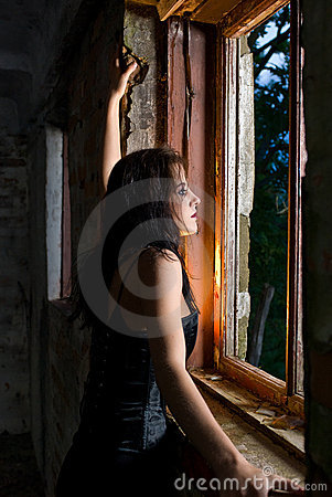 Goth woman looking out window