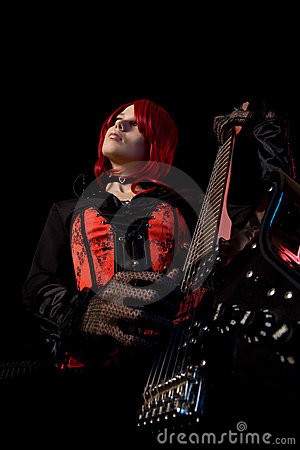 Gothic girl playing guitar, low angle view