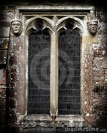 Gothic Stone Faces next to a church window