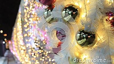 Gouden en rode glanzende ballen en slinger op witte spar De achtergrond van Defocused stock video