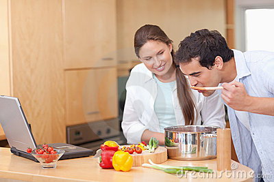 Gourmet couple using a laptop to cook