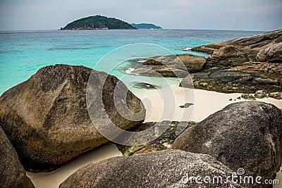 Göra perfekt den tropiska östranden och vaggar med turkoshavet på Sim