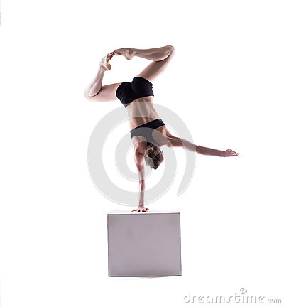 Graceful acrobat posing on cube