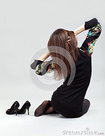 Graceful long-haired brunette sitting on the floor