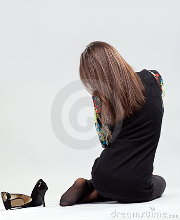 Graceful long-haired brunette sitting on the floor