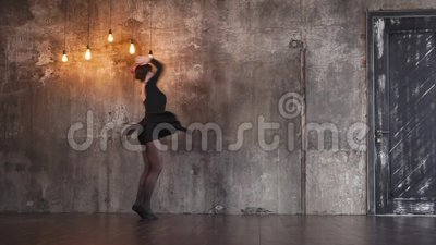 Trained dancer girl is swirling in a dramatic dance in a dark gothic hall. Graceful teenage girl is dancing romantic expressive dance. She is spinning in large stock video footage
