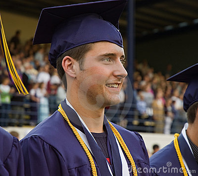 graduate in cap and gown with honor cords