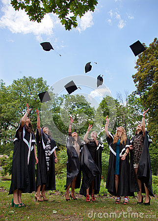 Graduates throwing  into the sky academic caps