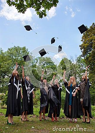 Graduates throwing  into the sky academic caps