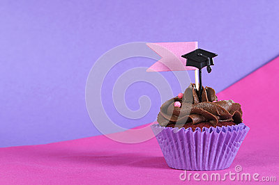 Graduation day pink and purple party cupcake with copy space.