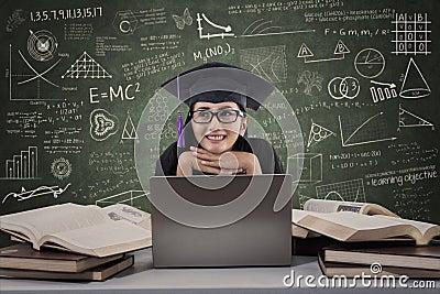 Graduiertes Denken der glücklichen Frau unter Verwendung des Laptops an der Klasse