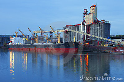 Grain elevators & cargo ship at dusk.