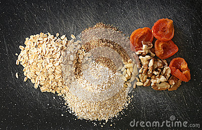 Grains, nuts, dry fruits on a black chopping board