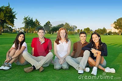 Grama verde do assento feliz dos povos do grupo dos amigos