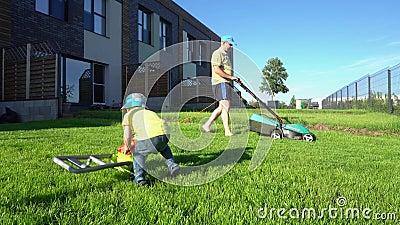 Gramado de sega do homem com cortador de grama quando jogo do filho com lawnmower do brinquedo suspens?o Cardan vídeos de arquivo