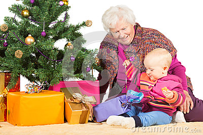 Gran and baby unwrapping Christmas gifts