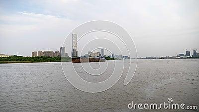 Gran barco de carga en un río con edificios en el fondo en un día nublado 4.000 almacen de metraje de vídeo