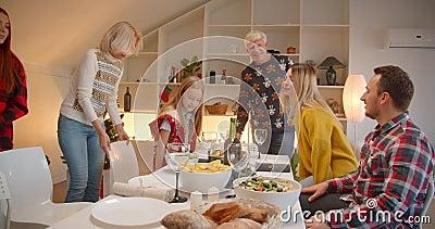 Gran familia caucásica sentada en una mesa navideña cena unión alegría sonrisa conversación comodidad en casa almacen de metraje de vídeo