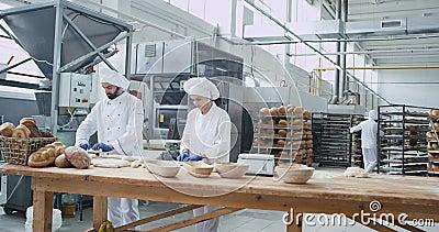 Gran industria panadería dos panaderos que trabajan en trozos concentrados de masa para hornear pan fondo gran panadería metrajes