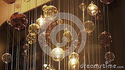 Grand lustre cher de verre dans un restaurant ou salle de concert Éclairage de lustre en Hall, Bokeh, éclat, lueur banque de vidéos