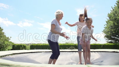 Grand-mère, petite-fille et mère rebondissant sur le trempoline banque de vidéos
