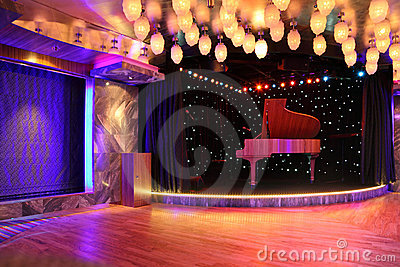 Grand piano on empty stage with many lamp