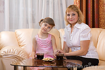 Grandchild and grandmother drink tea