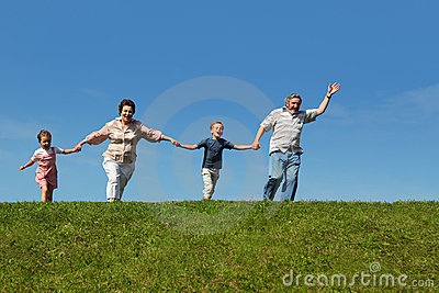 Grandchildren and grandparents running on hill Stock Photo