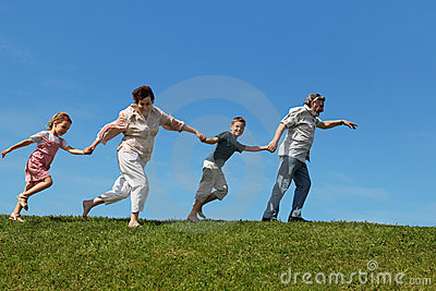 Grandchildren and grandparents running on lawn Stock Photo