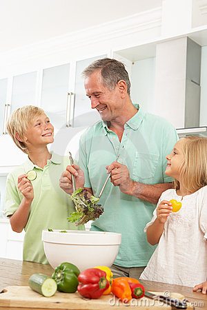 Grandchildren Helping Grandfather To Prepare Salad