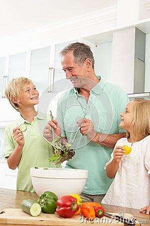 Grandchildren Helping Grandfather To Prepare Salad