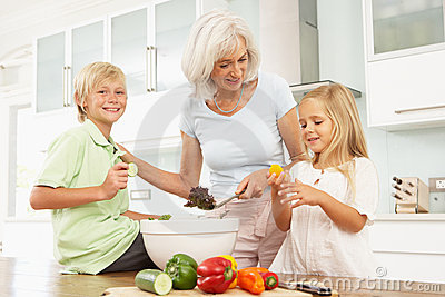 Grandchildren Helping Grandmother To Prepare Salad