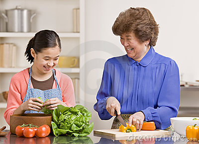 Granddaughter preparing salad with grandmother