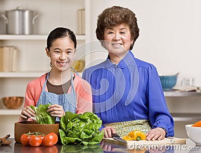 Granddaughter preparing salad with grandmother