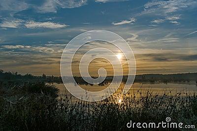 Grande por do sol enevoado sobre o pântano