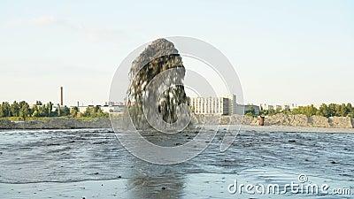Grande quantidade de água misturada à areia que bate de um tubo metálico contra um céu azul Extração de areia vídeos de arquivo