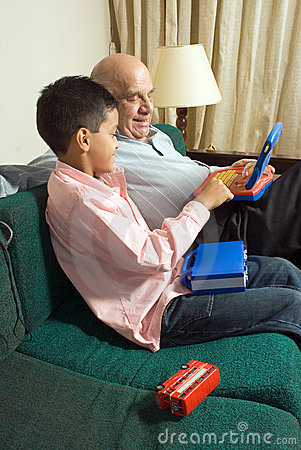 Free Grandfather And Grandson Sitting On A Couch - Vert Stock Image - 5478981