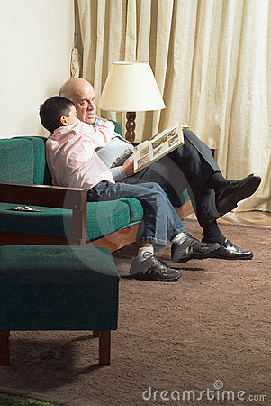 Free Grandfather And Grandson Sitting On Couch Reading Stock Photos - 5479743