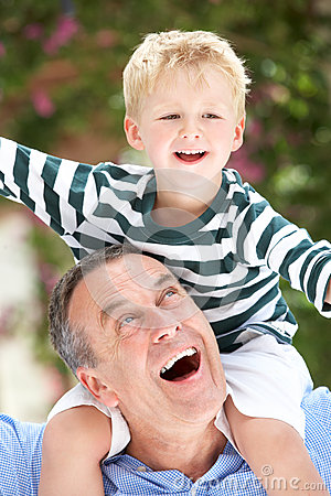 Grandfather Giving Grandson Ride On Shoulders