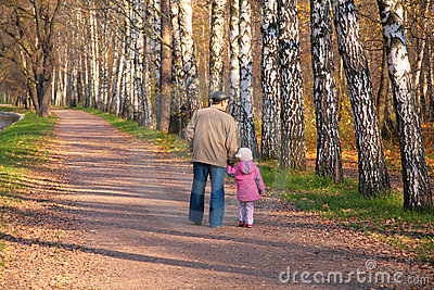 Grandfather with granddaughter walk in park