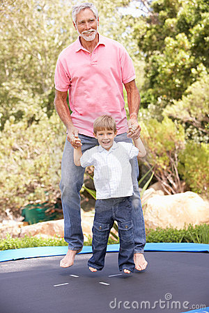 Grandfather And Grandson Jumping On Trampoline In