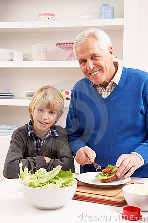 Grandfather And Grandson Making Sandwich In Kitche