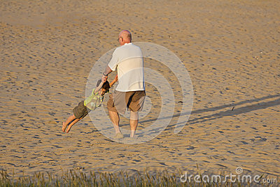 Grandfather and grandson playing on the beach