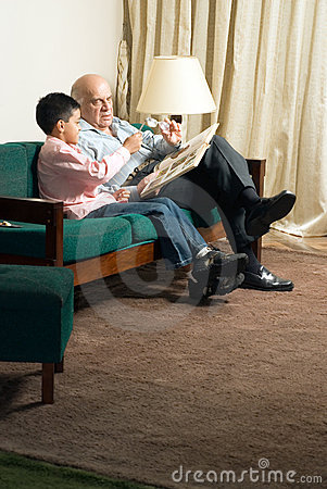 Grandfather and grandson sitting on the couch read