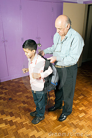 Grandfather helps grandson get ready for school -