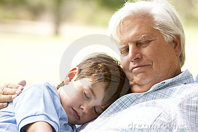 Grandfather Hugging Grandson In Park
