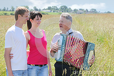 Grandfather play on accordion sing for couple